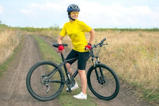 자연에 자전거와 함께 아름답고 행복한 여자 사이클