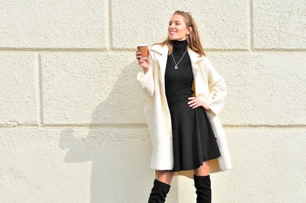 Красивая и счастливая женщина держит чашку кофе и стоит у уличной стены