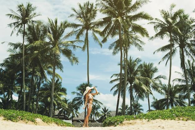 Красивая и счастливая женщина на пляже с пальмами