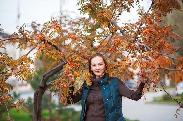 Красивая и счастливая женщина улыбается и гуляет в осенний парк.