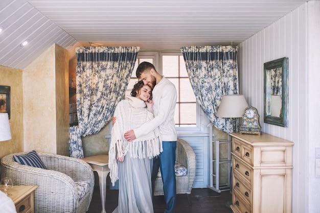 居心地の良い白いインテリアで自宅で美しく幸せな若いカップルの男性と女性