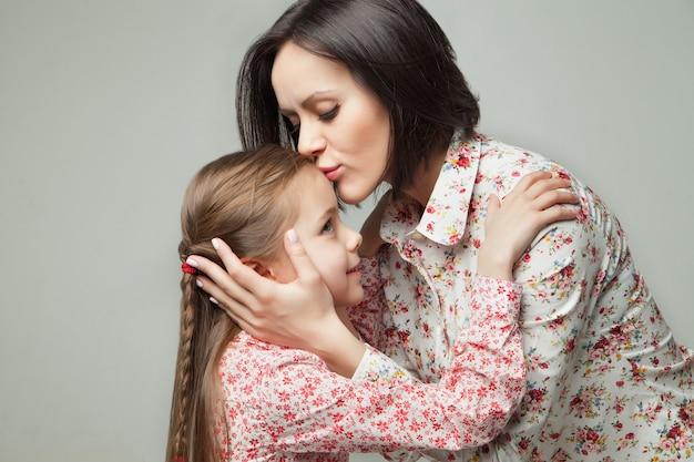 Красивая и счастливая молодая мать, целуя ее маленькую дочь. изолированные на белом фоне.