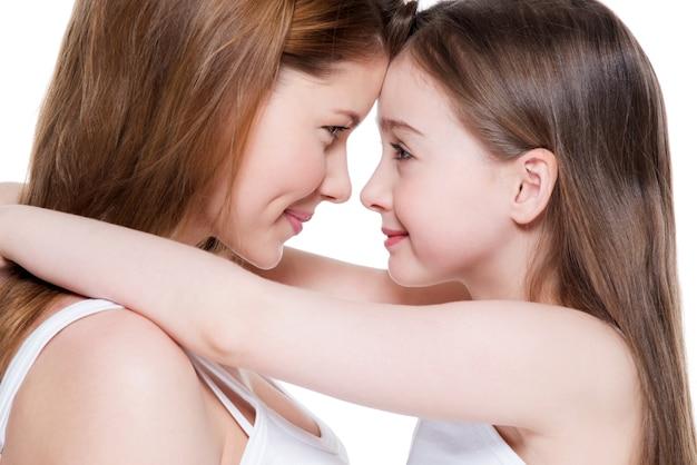 Красивая и счастливая молодая мама с маленькой дочкой 8 лет обнимаются в студии