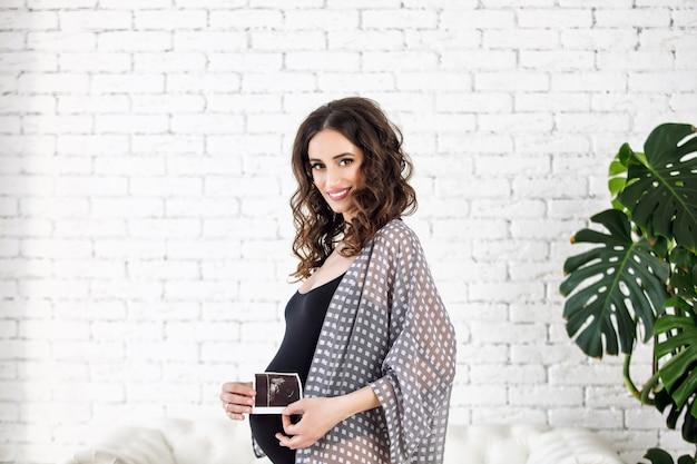 超音波の写真と明るいインテリアで自宅で美しく幸せな若い妊婦
