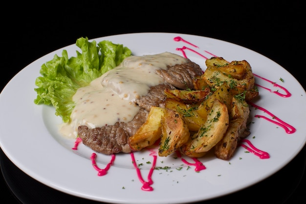 Красивая и здоровая еда на белой тарелке. жареное мясо, залитое соусом, картофель фри с укропом, зеленый салат. жареное мясо и картофель фри