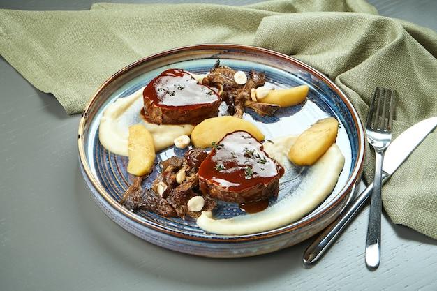 ふくらはぎ(ビーフ)テンダーロインの美しくジューシーなステーキと木製テーブルのブループレートにセロリクリームのピューレ添え。