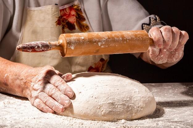 美しくて古い女性の手が生地をこね、そこからパン、パスタ、ピザを作ります。小麦粉の雲がほこりのように飛び交います。食品のコンセプト。