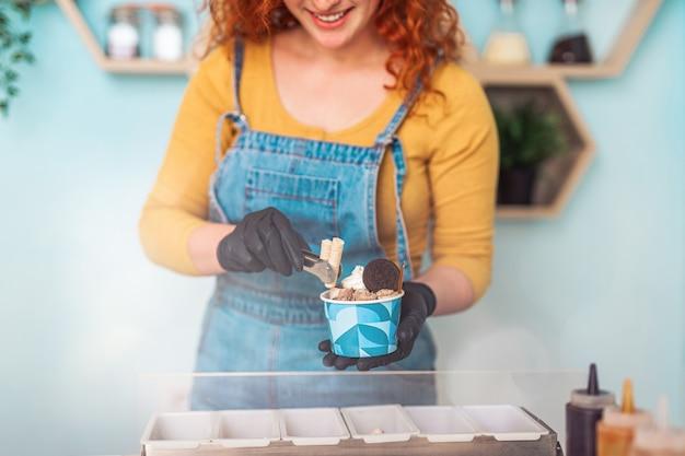 手作りのアイスクリーム店で笑顔で働いている美しくてポジティブな赤毛の生姜の女性。彼女はおいしいお菓子を準備して提供しています。