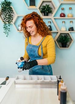 手作りのアイスクリーム店で笑顔で働いている美しくてポジティブな赤毛の生姜の女性。彼女はおいしい甘い食べ物を準備して提供しています。