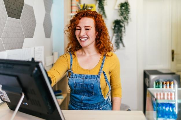 手作りのアイスクリーム店で笑顔で働いている美しくてポジティブな赤毛の生姜の女性。彼女は新しい顧客から注文を受けています。