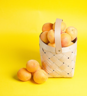 美しく熟したアプリコットは、黄色の壁に木製のバスケットにあります。