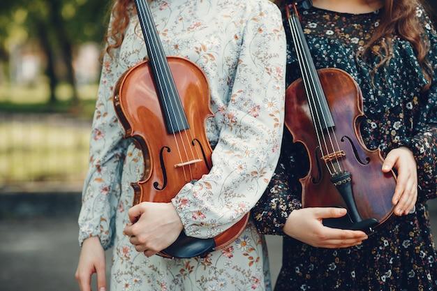 バイオリンのある公園で美しく、ロマンチックな女の子