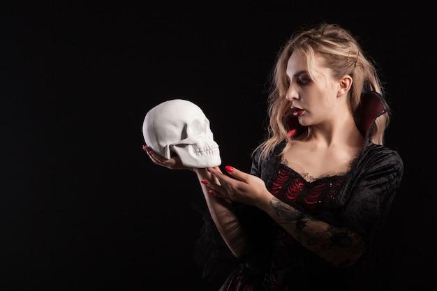 頭蓋骨を持って見ている吸血鬼のようにドレスアップした美しくセクシーなブロンドの女性。魅惑的な吸血鬼の女性。