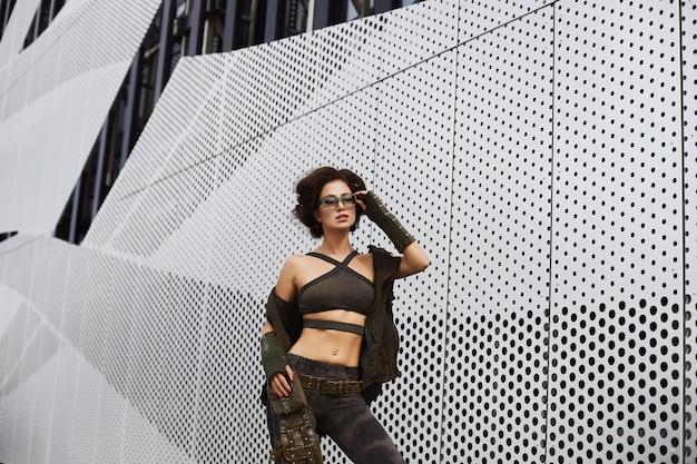 Красивая и сексуальная брюнетка модель с идеальным телом в стильных очках и в военной одежде с камуфляжным рисунком снимает жилет и позирует на улице в городе