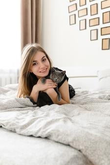 Красивая и сексуальная девушка лежит на кровати в самодельной пижаме, держа на руках счастливого шотландского серого котенка.