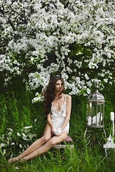 Красивая и сексуальная модель брюнетки с идеальным телом в стильном нижнем белье с белым голубем в руках позирует под цветущим деревом в зеленом лесу
