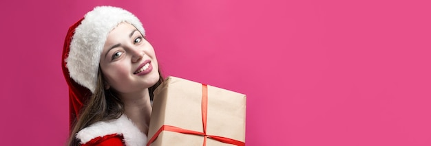 산타 클로스 의상을 입고 아름 답 고 섹시 한 여자입니다. 소녀는 크리스마스 선물을 들고 있습니다.