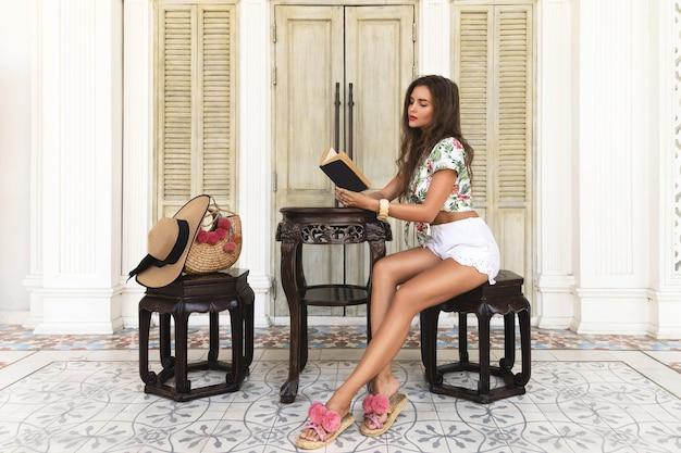 スタイリッシュな服を着て美しくセクシーな女性が本を読んでいます