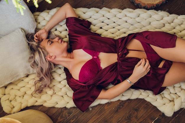 내실 침실에서 란제리를 입고 꿀 금발 머리를 가진 아름답고 섹시한 젊은 성인 백인 여자