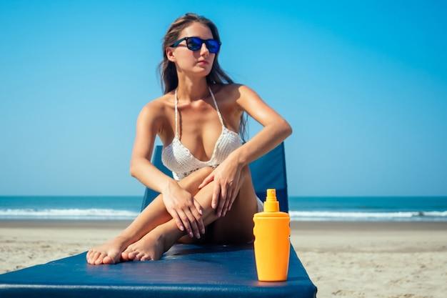 아름답고 섹시한 젊은 여자가 바다에 몸에 자외선 차단제를 적용하고 있습니다.