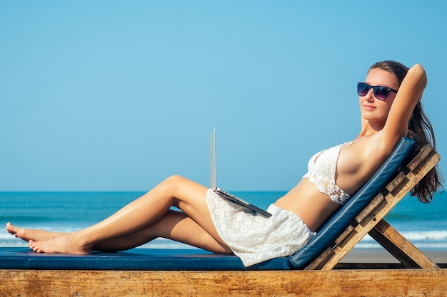 美しくセクシーな若い女性がデッキチェアに座って、海の上の彼女の膝の上にラップトップで休んでいます。女性フリーランサーはリゾートでラップトップで休んでいます