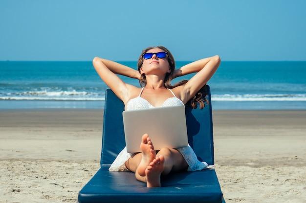Красивая и сексуальная молодая женщина лежит и отдыхает на шезлонге с ноутбуком на море. женщина-фрилансер с ноутбуком на курорте