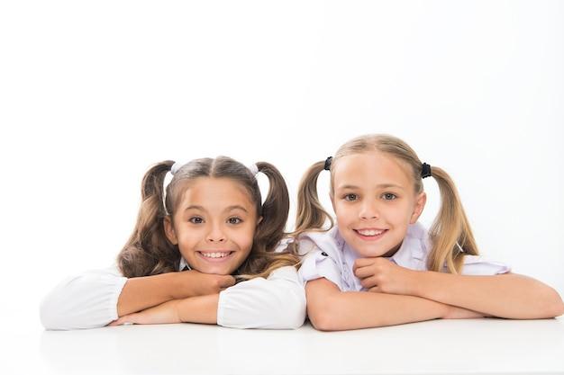 아름답고 똑똑합니다. 땋은 머리의 여고생. 흰색 절연 웃는 귀여운 소녀. 학교에서 행복한 작은 소녀들. 수업 시간에 사랑스러운 아기 소녀들.