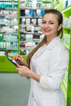 Красивый и улыбающийся фармацевт, работающий с планшетом