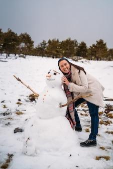 Красивая и улыбающаяся теплая женщина позирует рядом со снежной куклой - концепция отпуска - вертикальное изображение