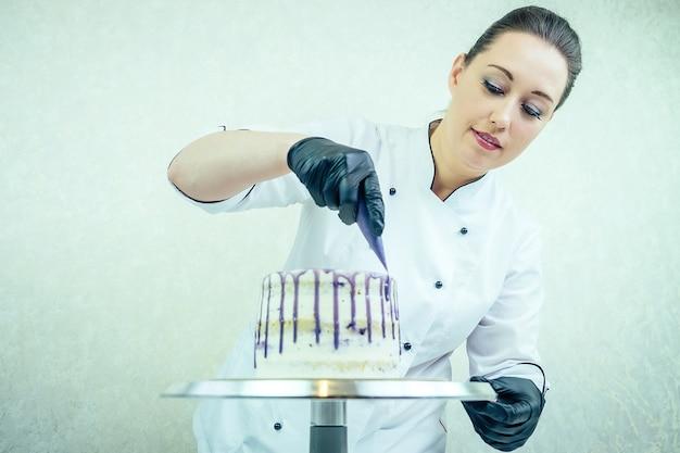黒の手袋と白い作業服を着た美しく笑顔の女性菓子屋がキッチンのケーキを飾ります。菓子屋、ケーキ、料理。ベリーと結婚式やバースデーケーキ。