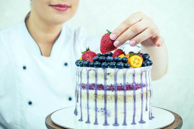 Красивая и улыбающаяся женщина-кондитер в белой рабочей форме украшает торт на кухне. кондитер, торт, кулинария. свадебный и праздничный торт с ягодами.