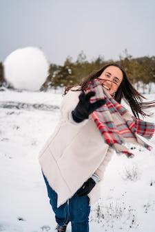 Красивая и улыбающаяся женщина, одетая в пальто, бросает снежки в камеру
