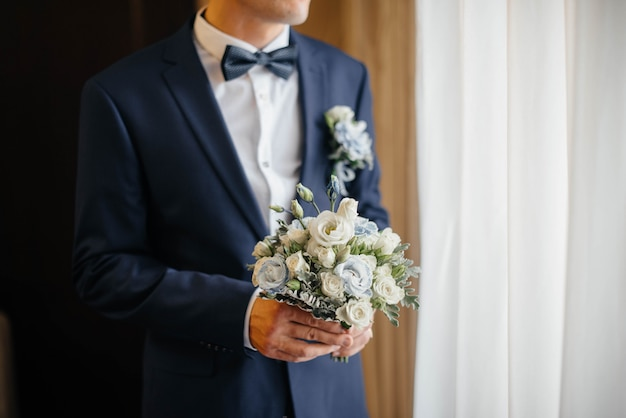 Красивый и изысканный свадебный букет крупным планом держит невесту в руках рядом с женихом. свадебный букет и кольца.