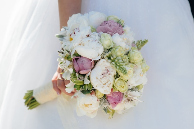 Красивый и изысканный свадебный букет крупным планом держит в руках невесту.