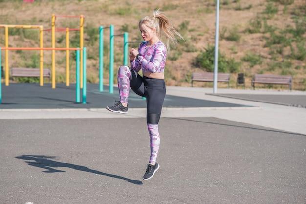 ストリートスポーツグラウンドでジャンプをしている美しくてスポーティーなブロンドの女性