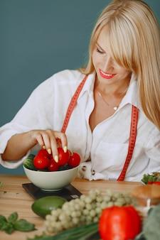 野菜とキッチンで美しくスポーティな女の子