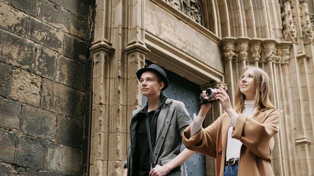 地図とカメラを持って通りを歩いている美しくてスタイリッシュな友達。彼らは、共同散歩のピークと魅力的です。