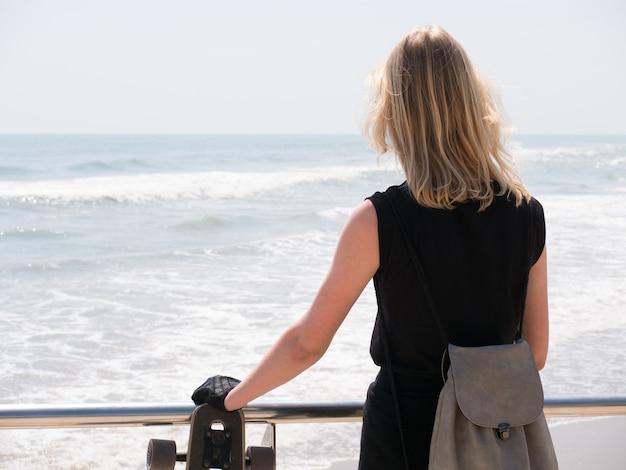 海辺でスケートボードでポーズをとる美しくてスタイルの若い女の子