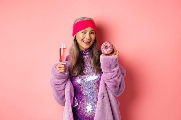 아름답고 세련된 아시아 노년 여성은 즐거운 시간을 보내고 샴페인을 마시고 달콤한 도넛을 먹고 카메라를 보며 웃고 분홍색 배경 위에 서 있습니다.