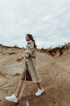 砂の風景を歩いて美しくスタイリッシュなアジアの女性。