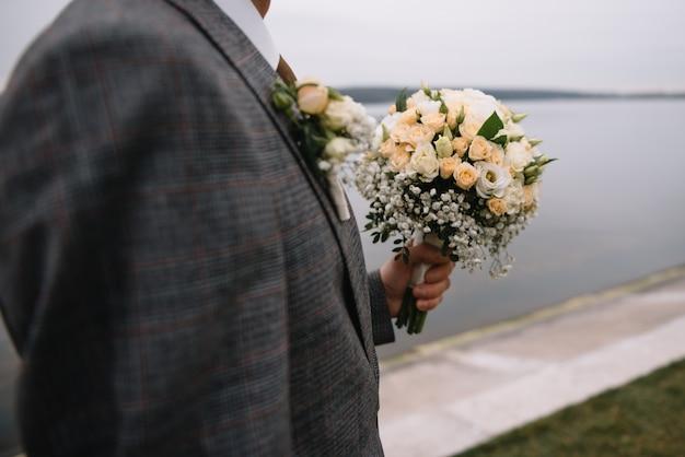 신랑의 손에 신부의 아름답고 세련된 꽃다발