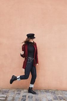 壁の前でポーズをとる、キャップ、コート、サングラスの美しくスタイリッシュな女の子。