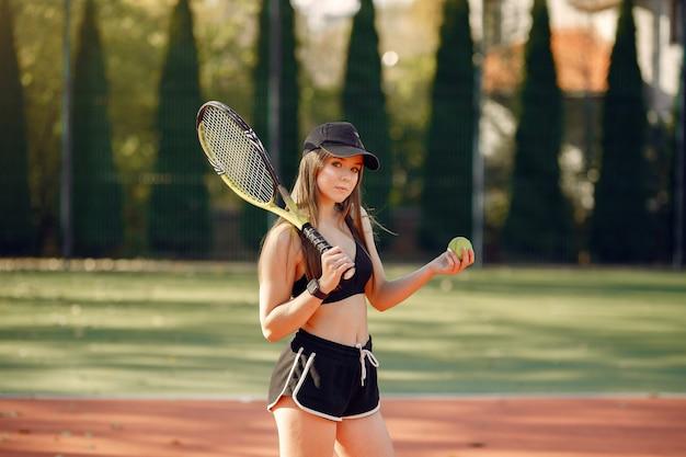 テニスコートで美しく、スタイリッシュな女の子