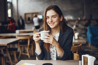 Beautiful and stylish girl sitting in a cafe and drink a coffee