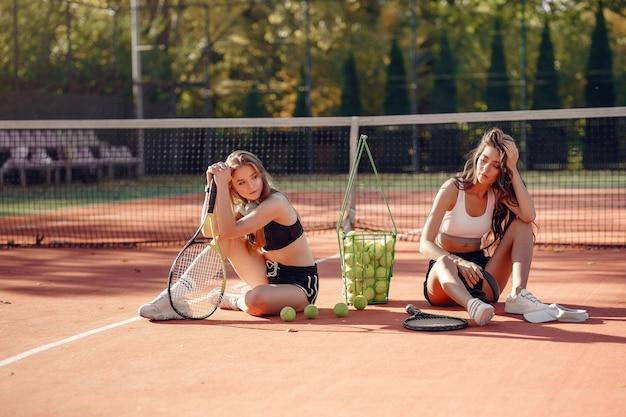テニスコートで美しくスタイリッシュな女の子