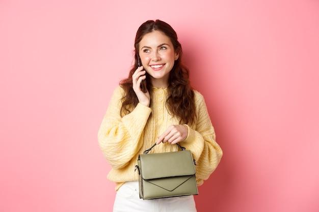 Красивая и стильная дама разговаривает по телефону, улыбается во время разговора с кем-то по мобильному телефону, держит кошелек, стоя у розовой стены