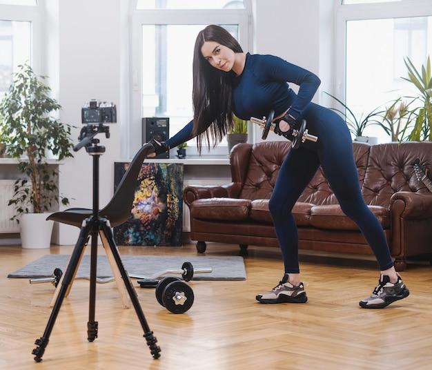 家具付きのモダンなアパートでカメラにポーズをとって椅子とダンベルで青い服を着た美しくスタイリッシュなスポーツウーマン。