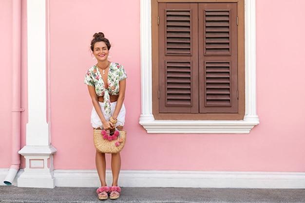 ピンクの壁で家の横にポーズをとっている夏服を着て美しくスタイリッシュな女性