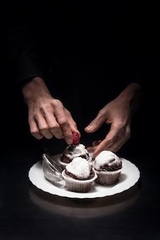 美しくておいしい。料理やレストランでシェフとして働いている間、カップケーキを飾る男の手のクローズアップ。