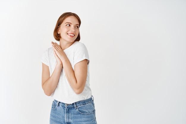 美しくて優しい自然の女の子、手を一緒に押して目をそらし、素敵なものを見て、白い壁に立っている